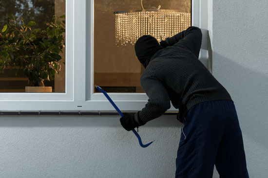 Злочинець хоче зламати вікно і проникнути в приміщення