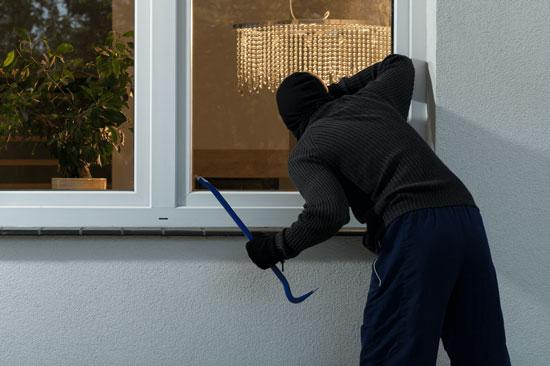Преступник хочет взломать окно и проникнуть в помещение